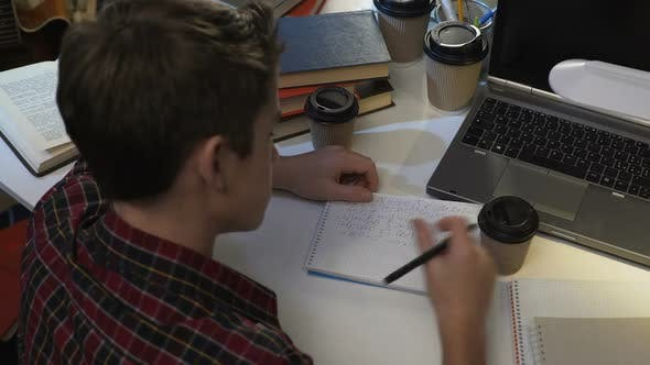 Thumbnail for Young man drinking tea or coffee and writing in notebook, exam preparation night