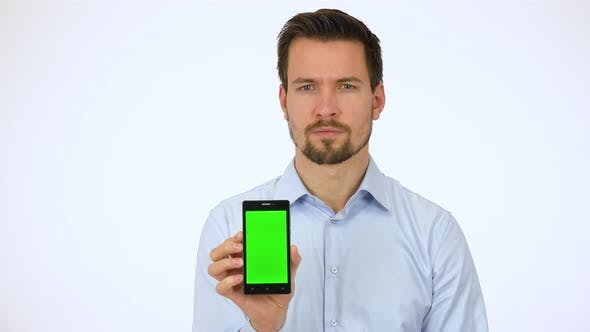 Thumbnail for A Young Man Shows a Smartphone with Green Screen To the Camera and Slowly Smiles - White Screen