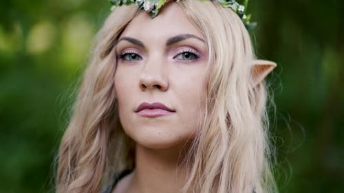 Portrait of Young Woman in Cosplay Elf Clothes and with Make-up on Green Background. Fantastic Look