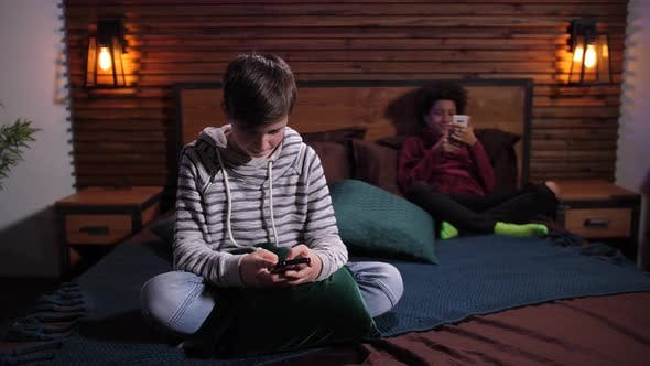 Diverse Teenagers Surfing the Net on Phones Apart