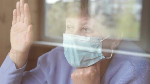 Woman on self-isolation is sad at the window
