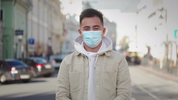Pandemic Portrait of a Young Asian Korean Tourist Man Wearing Protective Mask on Street Crowd People