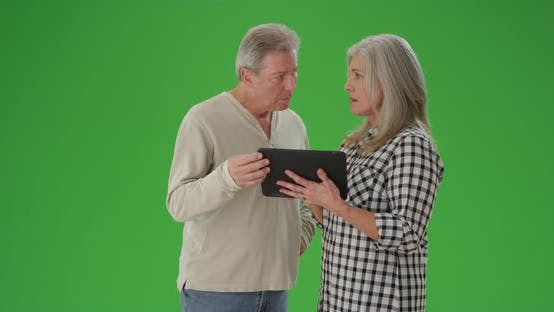 Thumbnail for Charming mature couple looking at tablet computer