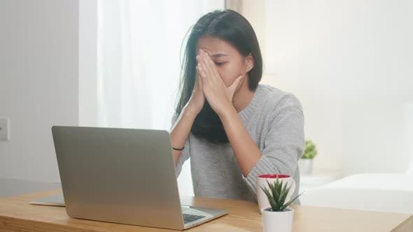 Asia women casual wear using laptop hard work in bedroom quarantine for coronavirus prevention.