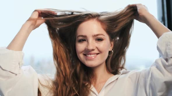 Cheerful Young Girl Playfully Touches Her Hair.