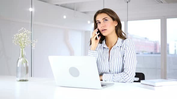 Cover Image for Hispanic Woman Talking on Phone at Work with Customer