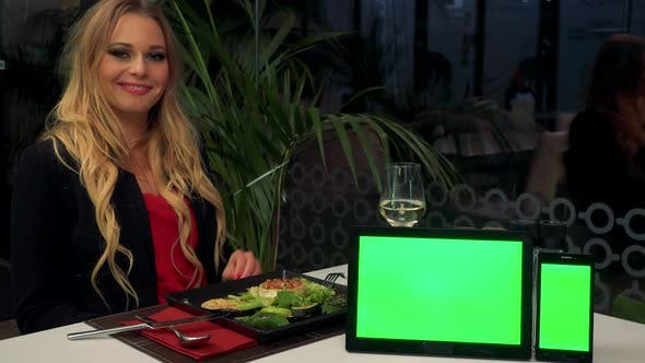 Thumbnail for A Woman Sits at Table in Restaurant, Smiles at the Camera - a Tablet and a Smartphone - Green Screen