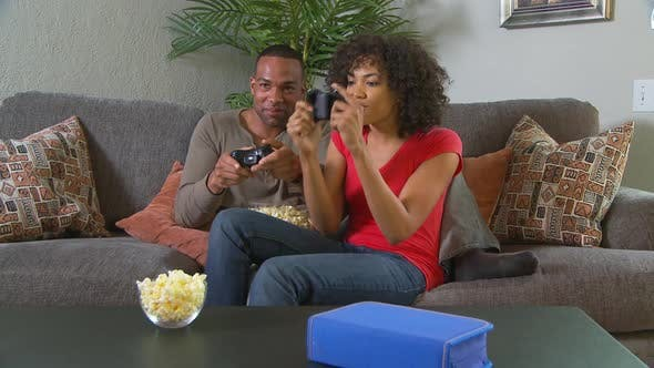 Thumbnail for Couple playing video games on couch