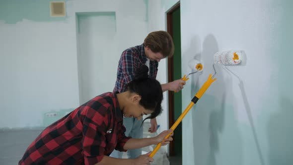 Thumbnail for Family Painting Interior Wall with Paint Rollers