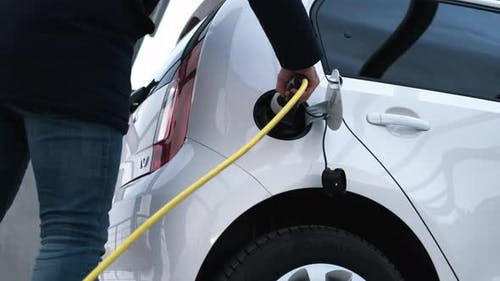 Close Up Man Hand Inserts Power Cable From Electric Car
