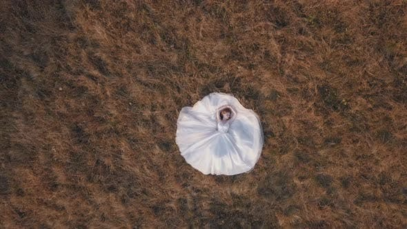 Thumbnail for Beautiful and Lovely Bride in Wedding Dress Lie on Grass on Field. Aerial View