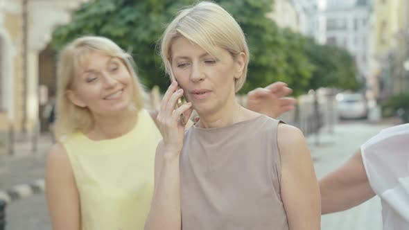 Thumbnail for Portrait of Stylish Mid-adult Woman Talking on the Phone As Friends Coming. Happy Female Caucasian