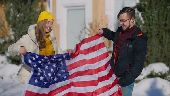 Smiling Young Millennial Couple Fluttering USA Flag Posing Outdoors