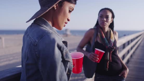 Black women best friends leaning against wooden railing of pier talking and holding red cups