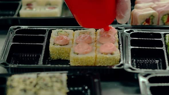 Cook Decorates with Cream Fried Japanese Rolls with Sesame.