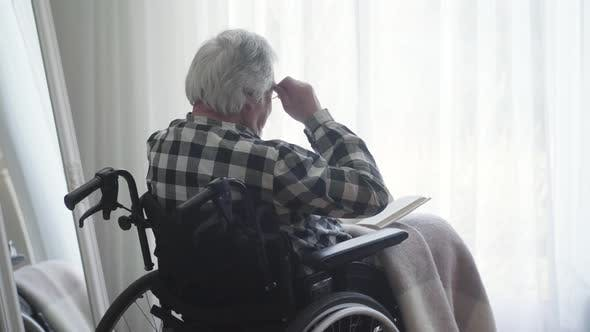 Thumbnail for Back Side View of Elderly Caucasian Man Putting on Eyeglasses and Reading Book. Disabled Old Retiree