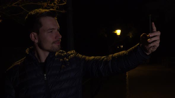Thumbnail for A Young Handsome Man Takes Selfies with a Smartphone in an Urban Area at Night - Streetlights