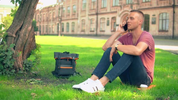 Thumbnail for Guy Sits Near the Tree Has Phone Conversation