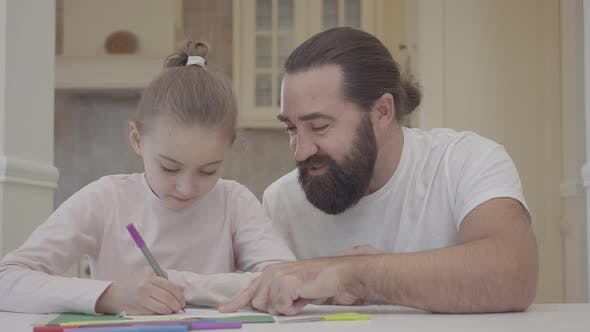 Thumbnail for Father and His Small Cute Daughter Are Sitting in Living Room and Drawing with Markers