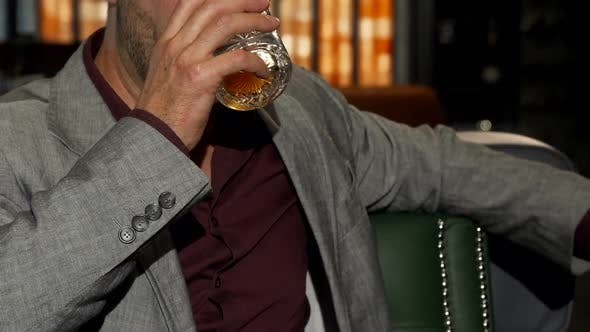 Cover Image for Handsome Mature Man Smiling To the Camera While Drinking Whiskey