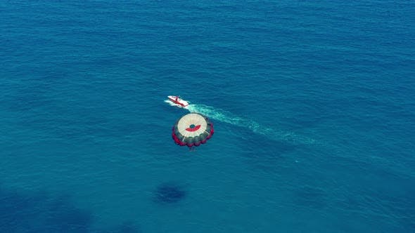 Thumbnail for Aerial View. Flying with Parachute Behind a Boat. Extreme Water Sport in the Sea. Parasailing.