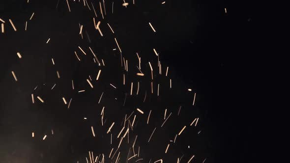 Campfire Sparks Rise Up Against Black Background. Slow Motion