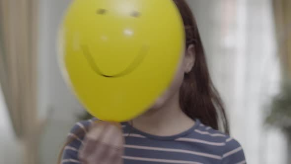 Thumbnail for A Pretty Girl Hiding Behind Yellow Balloon with a Painted Happy Face on It Then Puts It Down