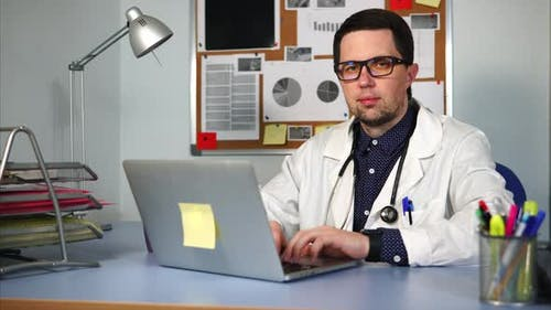 A Private Practice Doctor Sits at the Desk, His Hands on the Laptop Keyboard
