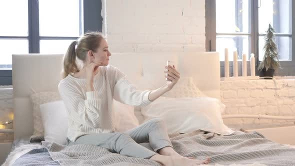 Thumbnail for Happy Woman Sitting in Bed Taking Selfie with Phone, Photograph