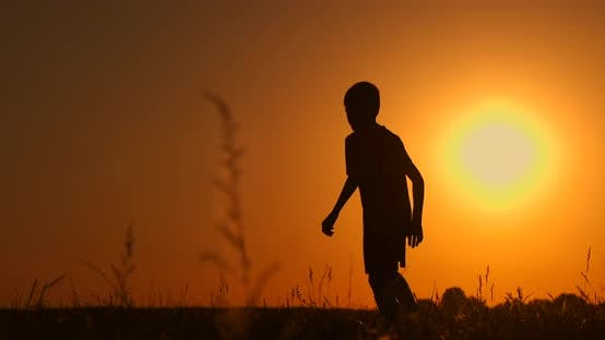 Thumbnail for Silhouette of a Boy Playing Football or Soccer at the Beach with Beautiful Sunset Background