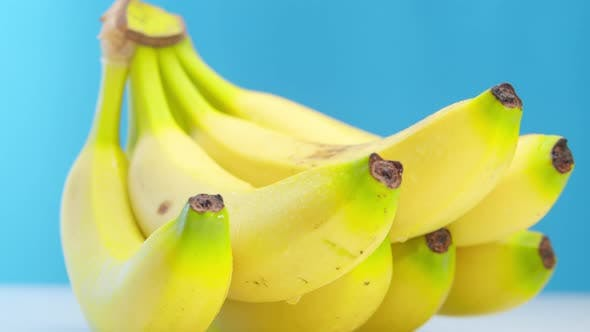 Beautiful Ripe Yellow Bananas with Drops of Freshness Lie on the Table on a Blue Background