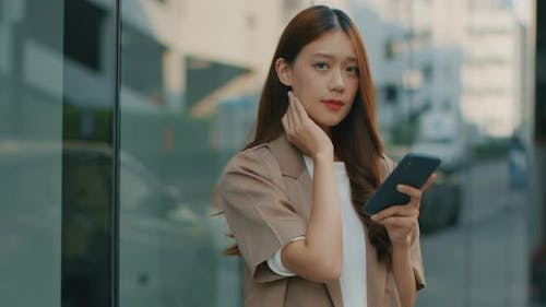 Asian Businesswoman using a mobile phone, working with a smartphone and looking at camera