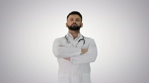Thumbnail for Young Male Caucasian Doctor Standing with Folded Hands on Gradient Background.