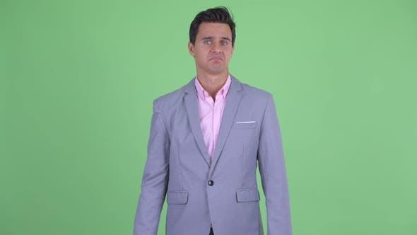 Confused Young Handsome Businessman Shrugging Shoulders
