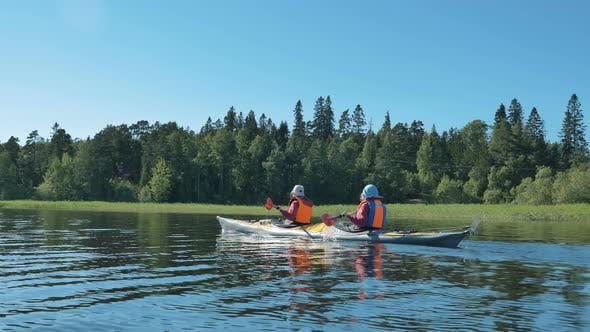Thumbnail for Man and Woman in Vests Sail Kayak Along Tranquil River