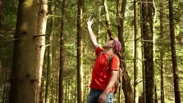 Male tourist looking for a cellular signal in a dense forest, camera tracking