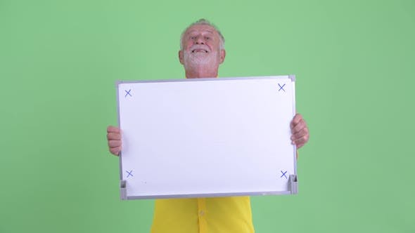 Cover Image for Happy Senior Bearded Businessman Holding White Board and Looking Surprised