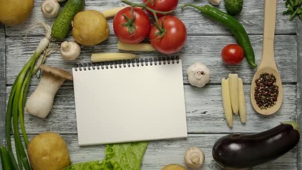 Thumbnail for Rezeptbuch auf Tisch mit Gemüse geworfen. Einfache Platzierung des Reciepe auf einem leeren Papier.
