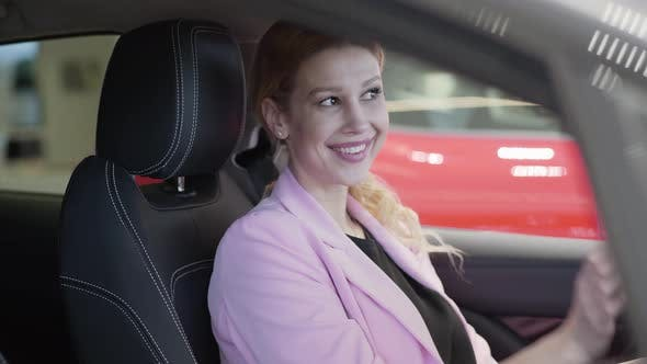 Thumbnail for Confident Smiling Woman in Pink Jacket in the Car, Looking in Rearview Mirror and Sending Air Kiss