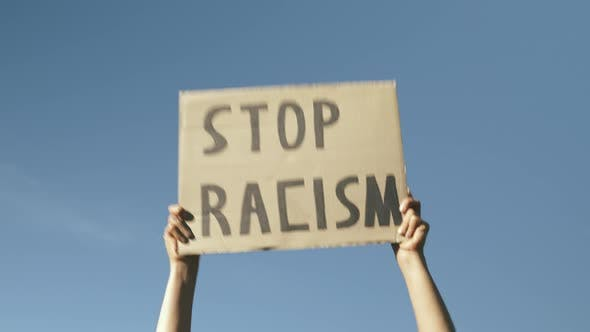 "Thumbnail for Poster STOP RACISM against blue sky. Hands against blue sky holding sign ""Stop Racism""."