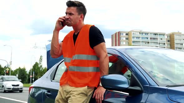 Thumbnail for Young Handsome Man Stands Next To the Car Dressed in Reflective Vest and Phones