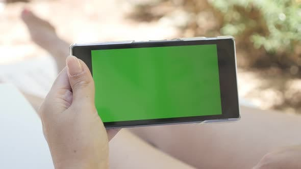Outdoor woman relaxing on deck-chair with green screen tablet 4K 2160p 30fps UHD footage - Young fem