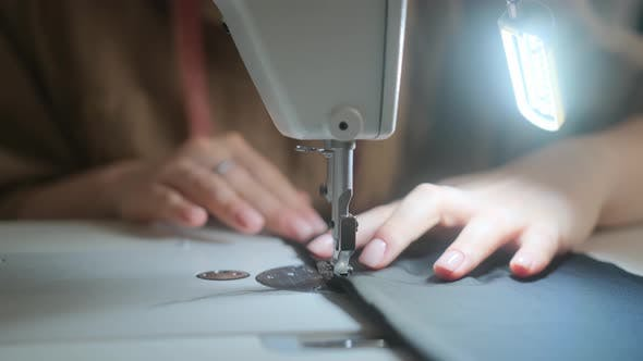 Stitching on sewing machine. Tailor sews on sewing machine. Close-up of woman's hand