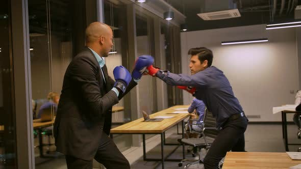 Two Competitive Businessmen Fighting with Boxing Gloves in Corporate Office