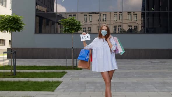 Thumbnail for Girl in Protective Mask with Shopping Bags Showing Sale Word Inscription During Coronavirus Pandemic