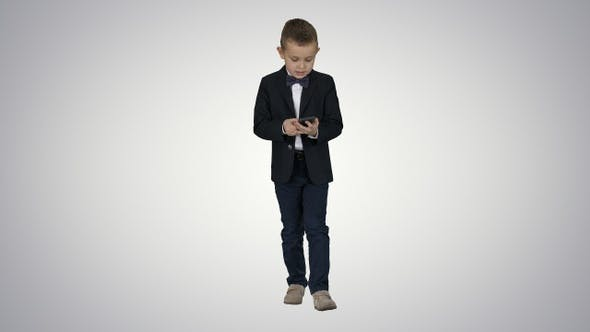 Thumbnail for Small boy in costume walking and using smartphone on gradient