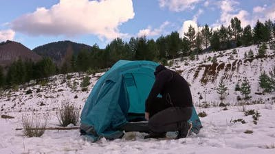 Hiker, arriving at tent, in the winter mountains