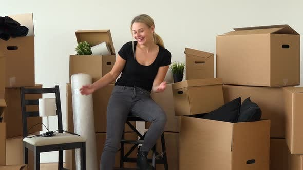 Thumbnail for A Happy Moving Woman Sits on a Chair in an Empty Apartment and Celebrates and Smiles