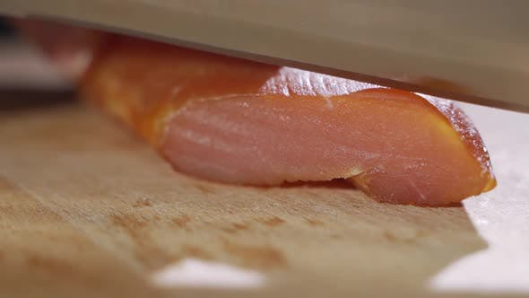 Cover Image for Chef Cuts Pieces of Raw Bacon By Sharp Knife on the Wooden Board