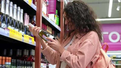 Shopping in Alcohol Department in Supermarket Woman is Choosing Champagne